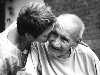 Woman kissing old man
